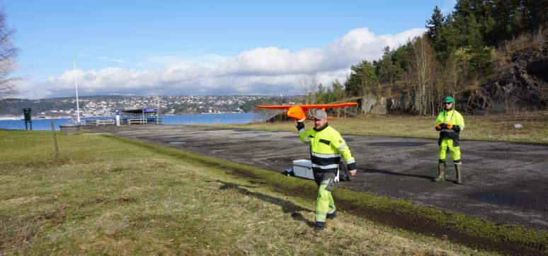 Scan Survey staff members preparing to launch a drone to collect data.