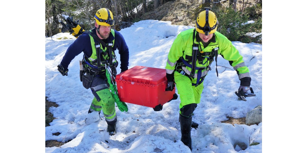 Staff wearing safety gear, carrying equipment in the snow and ice